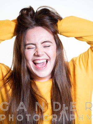 Portrait of woman in yellow jumper pulling on hair